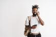 Photo of joyful african american guy using mobile phone and headphones