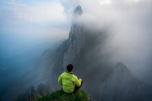 Happy Man Welcomes Daybreak Over Misty Valley On Top Of A Mountain And Enjoying The Day. Massive Rock Formation In The Swiss Alps, Unique Mountain, Swiss Alps Mountains At Saxer Lucke