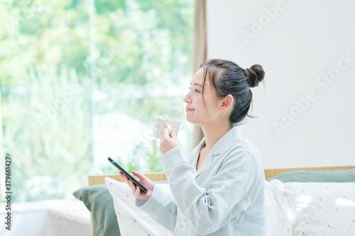 Photo 寝起きでスマートフォンを持つ女性