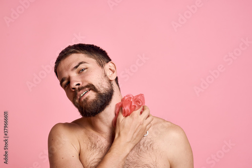 Fotografia Man with bare shoulders with a washcloth in hand taking a shower clean skin pink