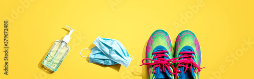 Fototapeta Fitness and coronavirus theme with running shoes - flat lay