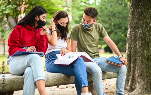 Three students studying together sitting on a bench outdoor and wearing masks during coronavirus times - 379675401