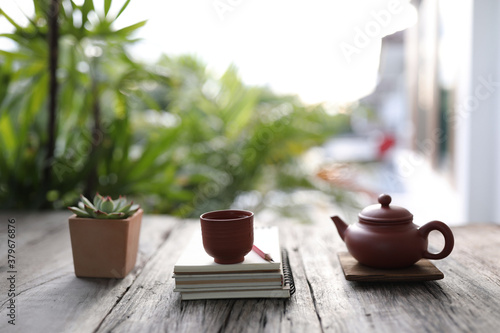 Fotografia Traditional clay teapot and tea pot with succulent plant with books on old woode