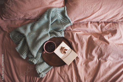 Cup of fresh coffee with open sketch book with fallen autumn leaf on wooden tray and knitted sweater in bed close up Wallpaper Mural