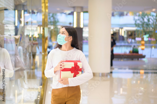 Woman wearing protective mask holding a gift box in shopping mall, shopping under Covid-19 pandemic, thanksgiving and Christmas concept.