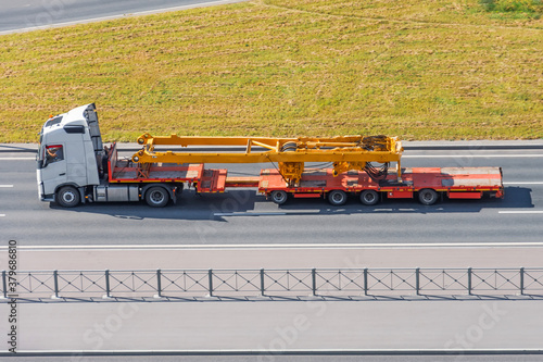 Transportation of tower jib crane components on pltaform truck trailers along the highway Wallpaper Mural
