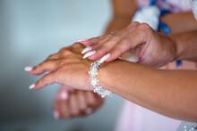 Bridesmaid Is Helping Bride To...