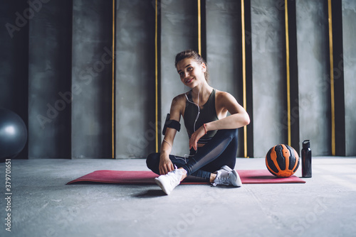 Obraz Half length portrait of professional prosperous woman in earphones resting after workout in gym, positive female athlete with ball looking at camera enjoying favorite songs from mobile phone - fototapety do salonu
