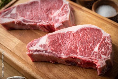 Obraz raw steak meat on cutting board in bright kitchen - fototapety do salonu
