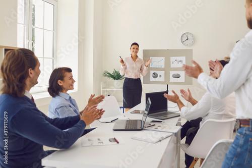 Fotografía Happy employees celebrating sales increase in corporate meeting with sales manag