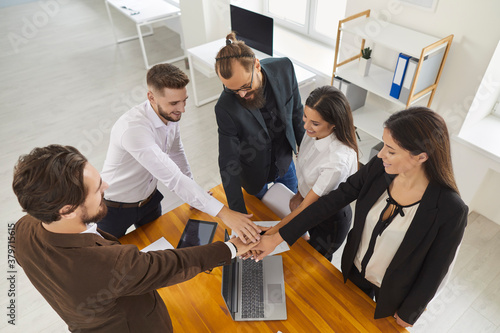Inspired business people joining hands making agreement and confirming collaboration