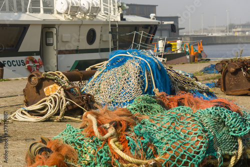colorful nets and rusty fishing gear on a quay in the harbor of Ostend, Belgium Fototapet