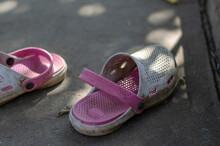 White-pink Dirty Summer Slippers In The Shade On A Concrete Path.