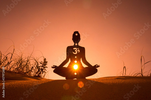 Fotografía Silhouette of a person doing yoga with the root chakra symbol