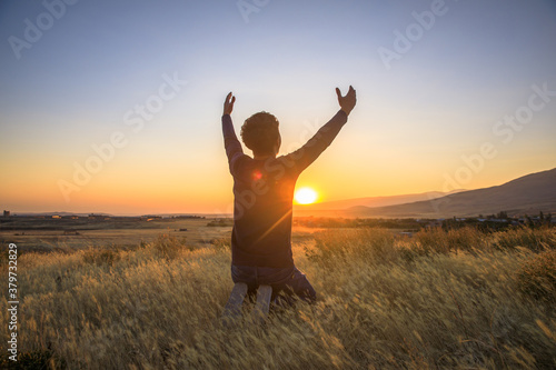Obraz man praying at the sunset - fototapety do salonu