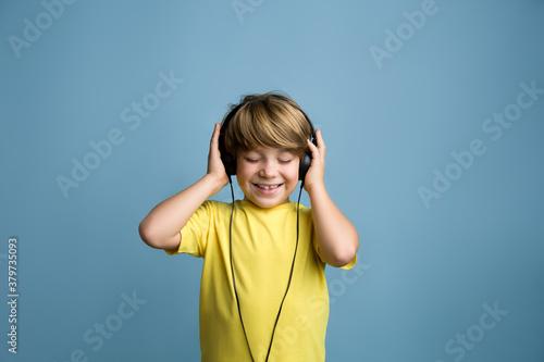 Obraz na plátně Fun young child enjoying rhythms in listening to music on headphones