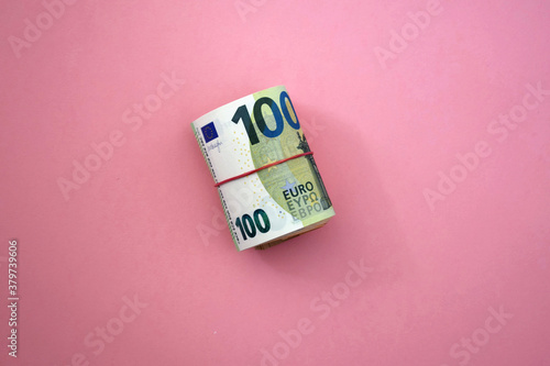 Roll of 100 euro banknotes with red rubber band on pink background. Roll of money.