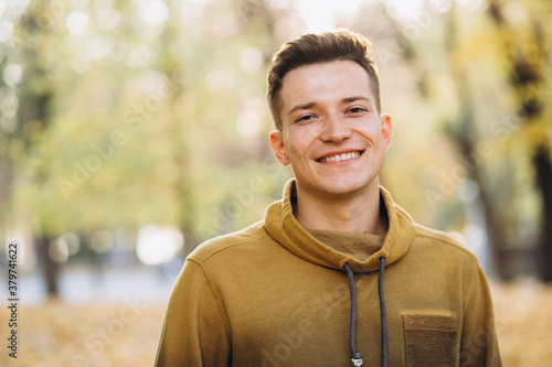 Fotomural Portrait of handsome guy smiling in the autumn park