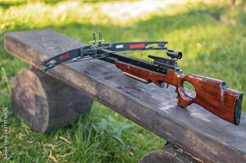 Photo Crossbow on a wooden bench. Selective focus.