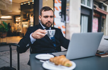 Caucasian Male Entrepreneur With Coffee Cup Watching Webinar Seminar During Breakfast Time In Street Cafe, Formally Dressed Businessman Reading Financial News About Trade Exchange Using Laptop App