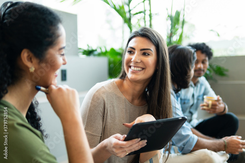 Charming brazilian female boss with tablet discussing sales strategy and planning in co-working open space Poster Mural XXL