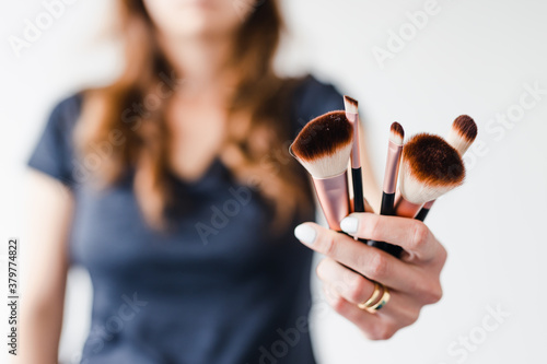 Obraz na płótnie girl holding make-up brushes in front of the camera showing the product, beauty