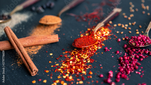Spices on wooden spoon displayed on a slate Fotobehang