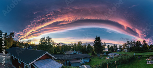 Miraculous panorama of sunset above scandinavian village with rose clouds - edge of cyclone. Arched dark sky with rose border to clear sky. Houses on green grass, crystal clear air. Fairy tale view
