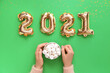canvas print picture - Hands with cup of hot chocolate and balloons in shape of figure 2021 on color background. New Year celebration