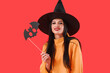 Beautiful young witch with Halloween decor on color background