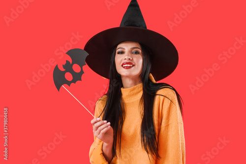 Fototapeta Beautiful young witch with Halloween decor on color background obraz