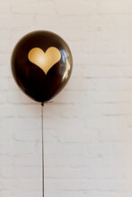 Black Latex Balloon Decorated With Gold Heart Floats In Front Of White Brick Wall
