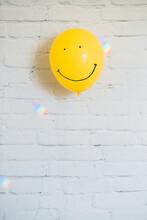 Smiling Emoticon On Balloon And Rainbow Light