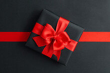 Gift Box And Red Ribbon On Bla...