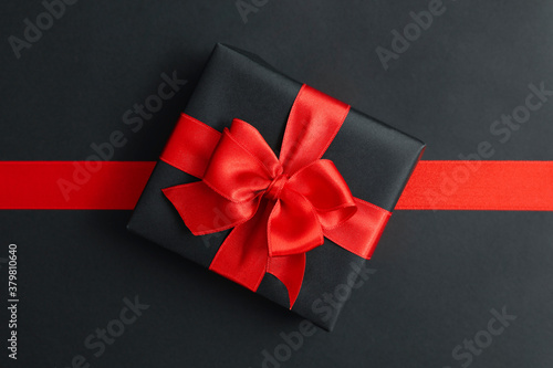 Gift box and red ribbon on black background Fotobehang