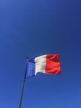 Flag Of France Waving Against Of Blue Sky