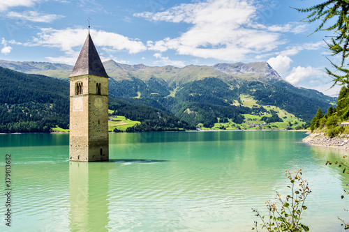 Leinwand Poster Church in the water at Lake Reschen in Tyrol in north Italy
