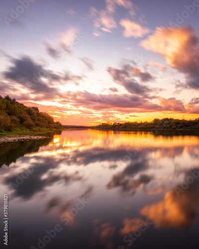 A sunset or sunrise scene over a lake or river with dramatic cloudy skies reflecting in the water on a summer evening or morning. #379818821