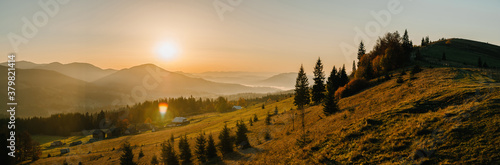 Panoramic autumn evening in the mountains. Trees on the edge of a hill in fall colors. The wonderful countryside in the morning. Amazing view on a sunny autumn day with fog and high mountain peaks.
