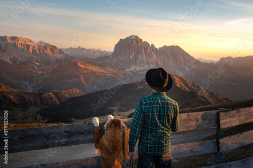 Fotomural a man with a red dog looking at the mountains