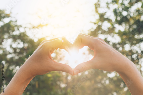 Fototapeta Female hands heart shape on nature bokeh sun light flare and blur leaf abstract background. obraz