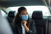 Young Attractive Businesswoman Having A Ride On A Backseat Of A Taxi During Covid-19 Pandemic Wearing Mask. Business Trips During Pandemic, New Normal And Coronavirus Travel Safety Concept.