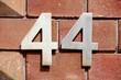 canvas print picture - Weisses Hausnummernschild Nr. 44 auf rötlicher Backsteinmauer, Deutschland, Europa