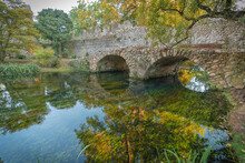 Stone Bridge With Arches And Reflection In The Water In The Nymph Gardens In The Province Of Latina In Italy