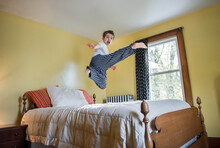 Child Does A Flying Sidekick While Jumping On His Bed
