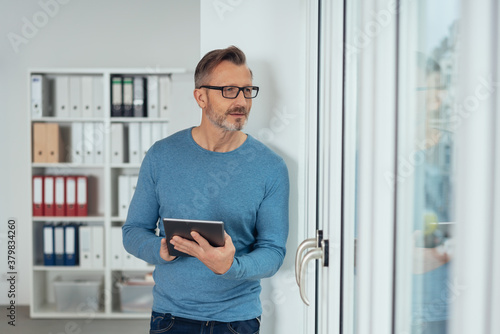 Distracted businessman peering out of a glass door Wallpaper Mural