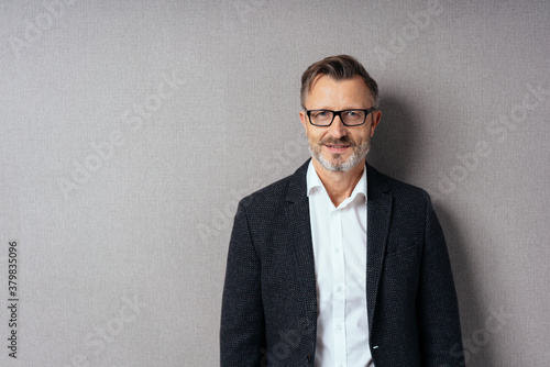 Middle-aged man in suit and glasses on grey Fototapet