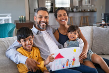 Happy Ethnic Family Showing Painting With New Home