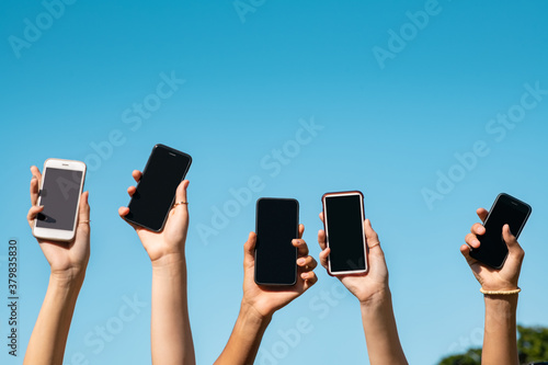Fototapeta Group of hands showing smartphone with copy space obraz
