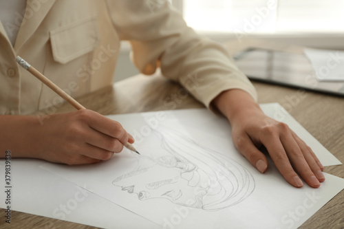 Woman drawing girl's portrait with pencil on sheet of paper at wooden table, closeup